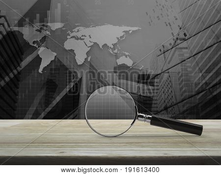 Magnifying glass on wooden table over black and white world map with modern city tower Business analyzing concept Elements of this image furnished by NASA