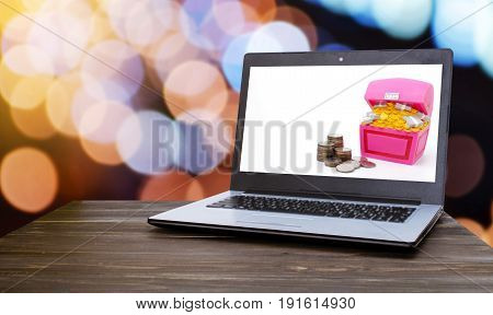 Laptop computer with piggy bank or treasure chest shaped money box with coins on white background with blurred night light bokeh background online financial saving money and technology concept
