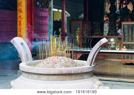 Burning incense sticks in Chinese temple in Vietnam