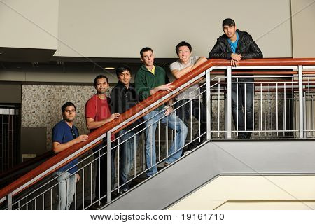 Group of Diverse College Students standing at the stairs inside a University building