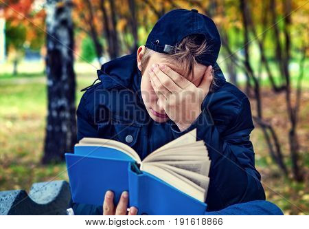 Sad Teenager with the Book in the Autumn Park