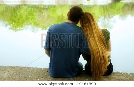Romantic couple hugging and sitting on lakeside