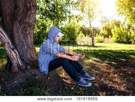 Teenager with Tablet Computer under the Tree outdoor