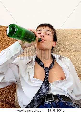 Young Man drinks a Beer on the Sofa at the Home