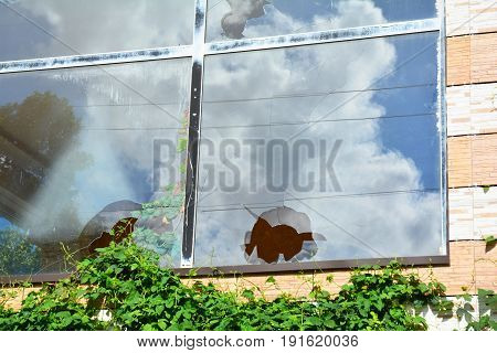 Broken glass window reflecting cloudy sky. A house window with a broken window pane after refuges riot.