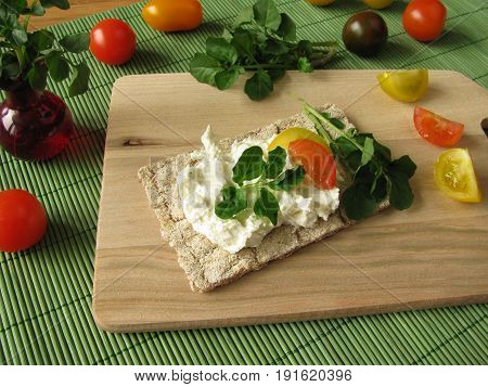 Cream cheese with watercress on crispbread on cutting board
