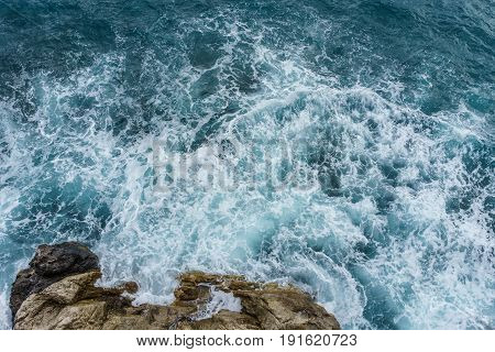 Danger sea ocean wave crashing on rock coast with spray and foam before storm in Autum Positano Italy.