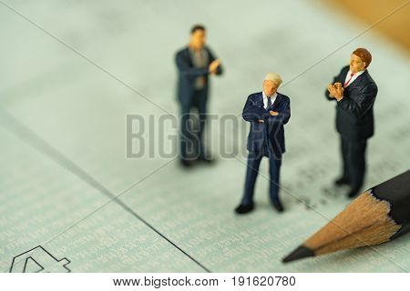 Miniature people small figure businessman standing on bank account book and others clapping as business financial concept.