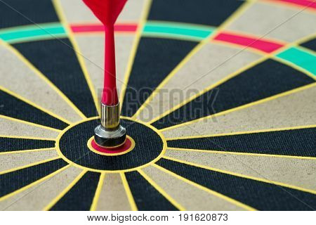 Business goal or target concept with a magnetic red dart in the center of dartboard.