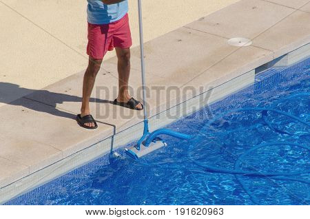 Man Cleaning The Swimming Pool With A Vacuum Head