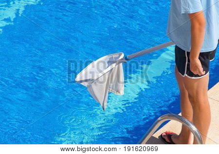 Man Wearing Shorts Cleans The Swimming Pool With A Net