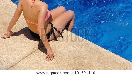 Young Woman In Swimwear Sitting On The Poolside