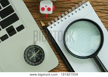 SEO search engine optimization concept with pencil compass computer robot and magnifying glass in flat lay.