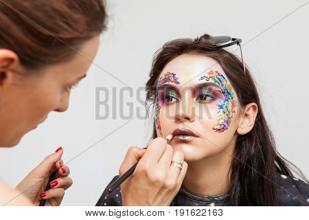 Make-up artist working on model lips before photo shooting. Beauty and fashion. Creativity and makeup. Cosmetics and backstage preparation for photo shooting