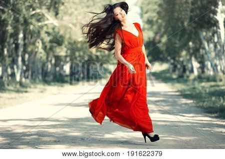 Asian lady in red dress running outdoors