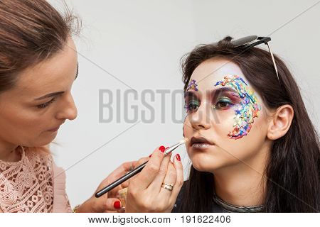 Make-up artist working on beautiful model lips before photo shooting. Beauty and fashion. Creativity and makeup. Cosmetics and backstage preparation for photo shooting