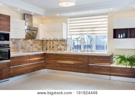 Modern design of the kitchen in a light, bright interior. Kitchen wood facades are made from walnut veneer.