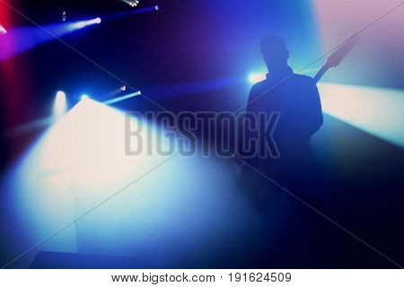Rock guitarist silhouette on stage at concert. Abstract image.