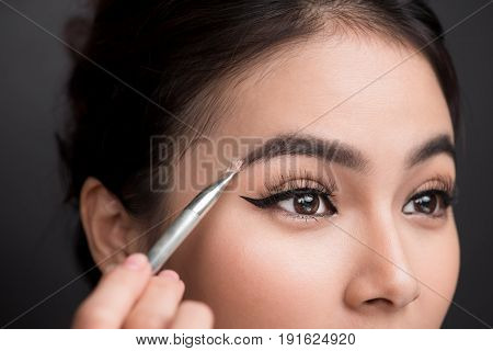 Close Up Of Beautiful Face Of Young Asian Woman Getting Make-up. The Artist Is Applying Eyeshadow On