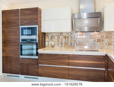 Modern home interior. Modern design of the kitchen in a bright interior. Kitchen wood facades are made from walnut veneer. Kitchen and living room combined. European furniture, design, technologies.