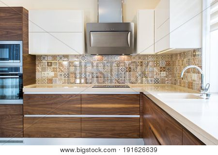 Modern design of the kitchen in a bright interior. Front view. Kitchen and living room combined. Kitchen wood facades are made from walnut veneer. European furniture, design, technologies.