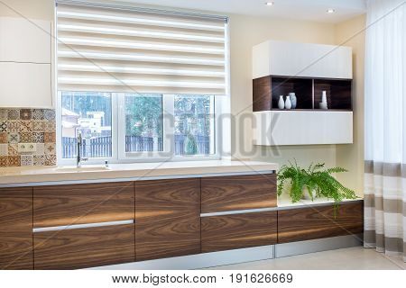 Modern home interior. Modern design of the kitchen in a bright interior. Kitchen and living room combined. Kitchen wood facades are made from walnut veneer. European furniture, design, technologies.