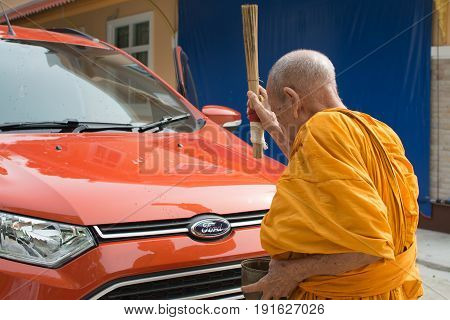 PhatthalungThailand May 07 2017 : Unidentified monk sprinkle holy water on a new car (Orange Ford ecosport) for the owner's lucky and safety the transfer ceremony of new car.