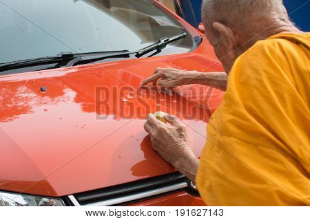 PhatthalungThailand May 07 2017 : Unidentified monk anoints holy powder on a new car (Orange Ford ecosport) for the owner's lucky and safety the transfer ceremony of new car.