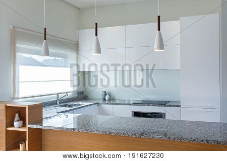 Modern kitchen design in light interior with wood accents. There is also a kitchen peninsula in the room. Kitchen and living room combined.