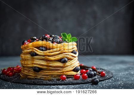 Pancakes with fresh berries and maple syrup on dark background closeup