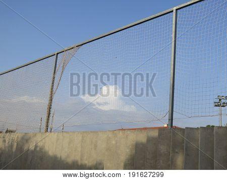 Cloud behind foorball stadium netting in Andalusian village