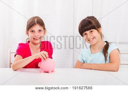 Cute little girls putting coin into piggy bank.