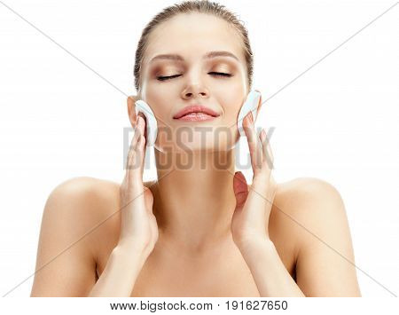 Sensual beautiful woman with flawless skin is holding cotton pads near face. Photo of blonde woman on white background. Skin care concept