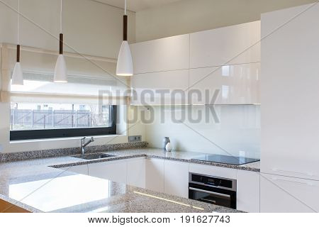 Modern kitchen design in light interior with wood accents. There is also a kitchen peninsula in the room. Kitchen and living room combined. European furniture, design, technologies. Stone surface.