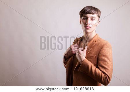 Man in naked torso wearing a fashion jaket on gray background in studio photo