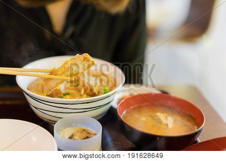 Woman hands eating katsudon or tonkatsu set with miso soup in bowl on restaurant