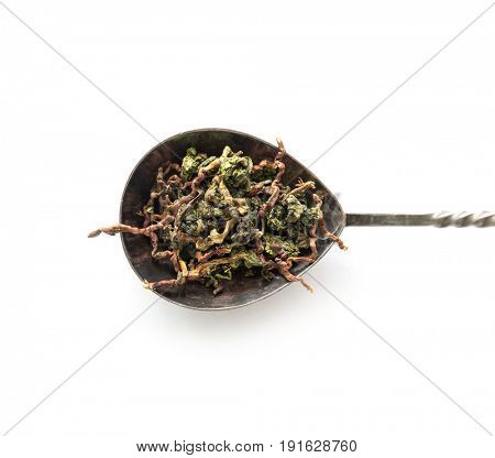 Metallic spoon with loose tea of different kinds, topview, closeup, delicious tea