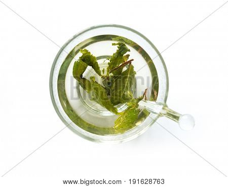 Aromatic fresh green tea brewed in a simple glass cup, loose leaves, topview