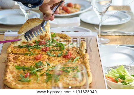 Cutting A Delicious Italian Pizza With Cheese, Mushrooms, Artichokes And Tomatoes With Help Of Knife