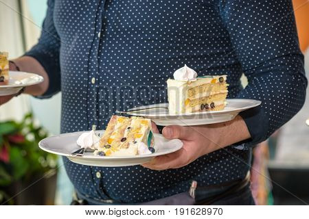 Waiter Carries Plates With Desserts Of Cakes