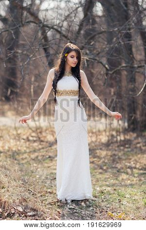 Braided bride at forest in white dress on blurred autumn background during a wedding photo shoot. Young beautiful woman with flowers in hair
