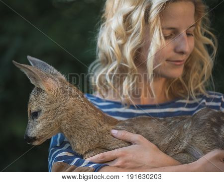 Young beautiful woman hugging animal ROE deer fawn in forest