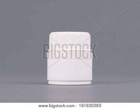 Blank medium size medicine white plastic packaging bottles for cosmetics, vitamins, pills or capsules.