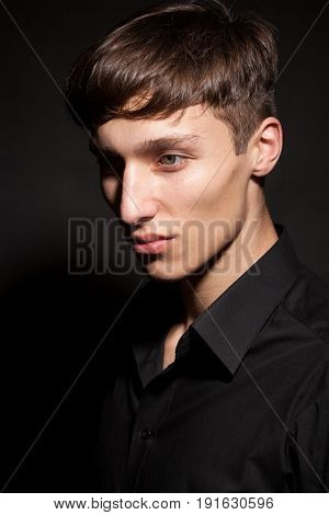 Male model on black background in studio photo. Expression and style