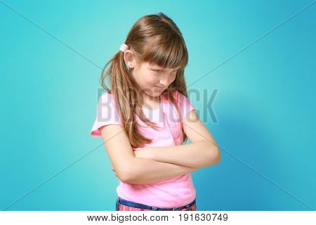 Displeased little girl on color background