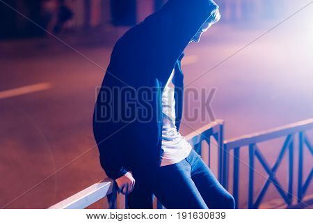 Young sad casual student in hood outdoors. Portrait of hooded guy walking through night city