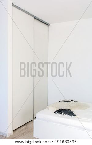 Modern home interior. Built-in wardrobe in the light interior of the bedroom. Small room. One room apartment where the kitchen is combined with the bedroom. European furniture, design, technologies.