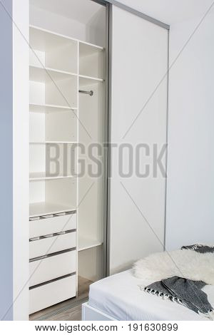 Built-in wardrobe in the light interior of the bedroom. One room apartment where the kitchen is combined with the bedroom.