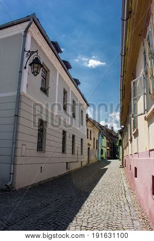 Medieval street view in Sighisoara citadel ,Romania. Dramatic colorful sky