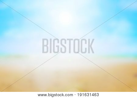 Blurred background of the sand, water and sky of a beach.